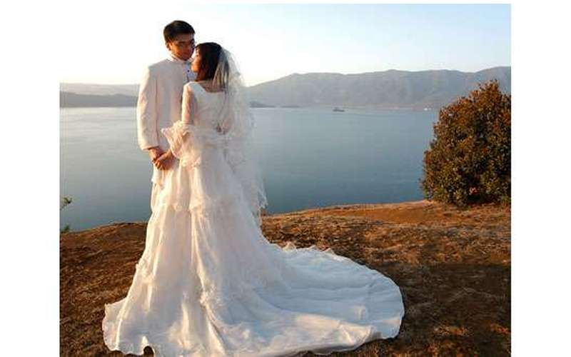 Bride and groom in front of a lake and surrounding mountains