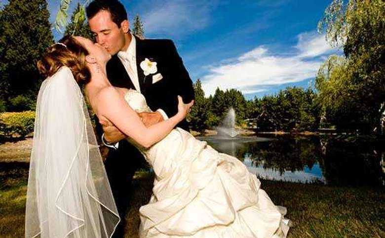 Bride and groom kissing in front of a fountain