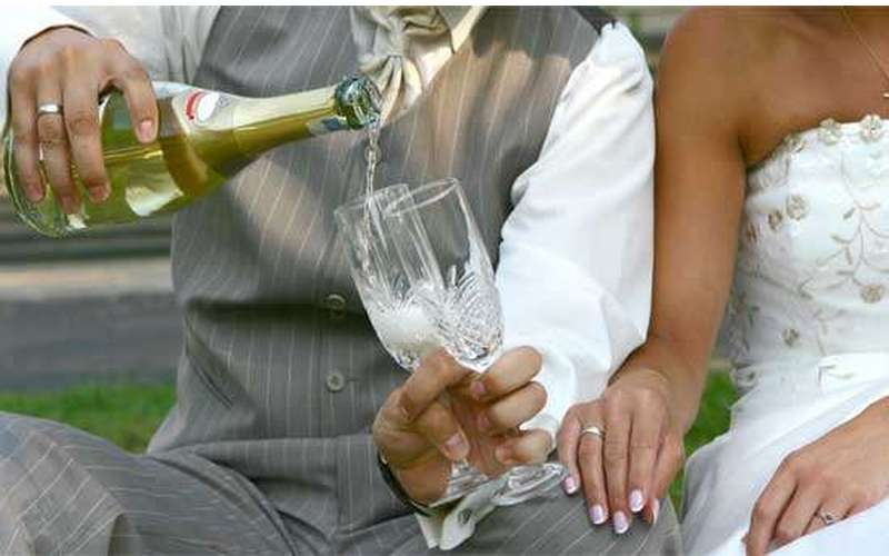 Groom pouring champagne for himself and his bride