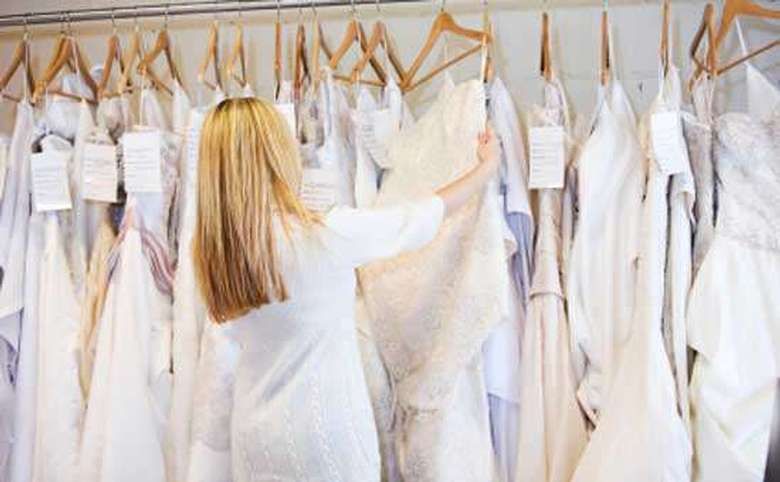 Woman looking through a rack of wedding dresses