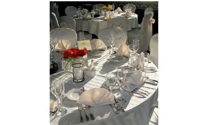Tables set for a wedding, complete with silverware, linens, and centerpieces