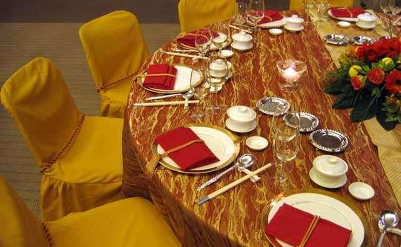 table set for a wedding with mustard chair covers and red napkins