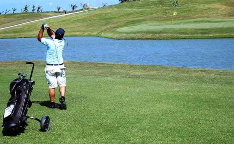 man in a light blue shirt in the end portion of a golf swing