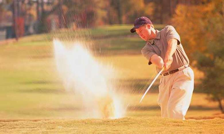 golfer performing a chip shot while sand sprays up