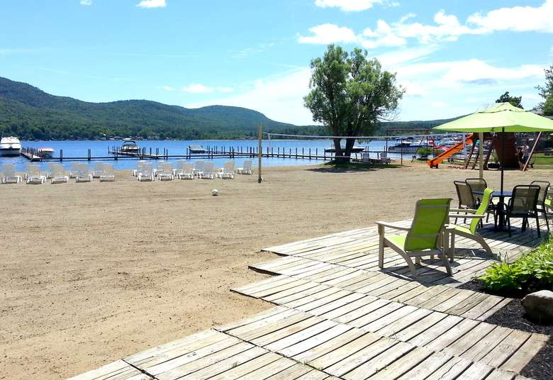 colorful chairs and a sandy beach overlooking lake george
