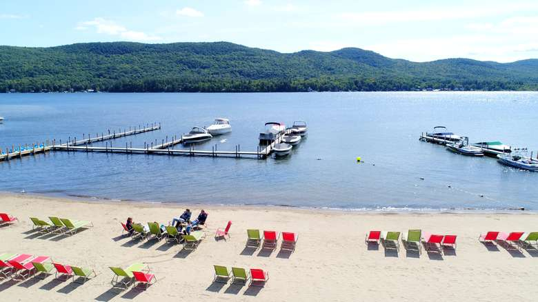 colorful lounge chairs on a beach overlooking lake george