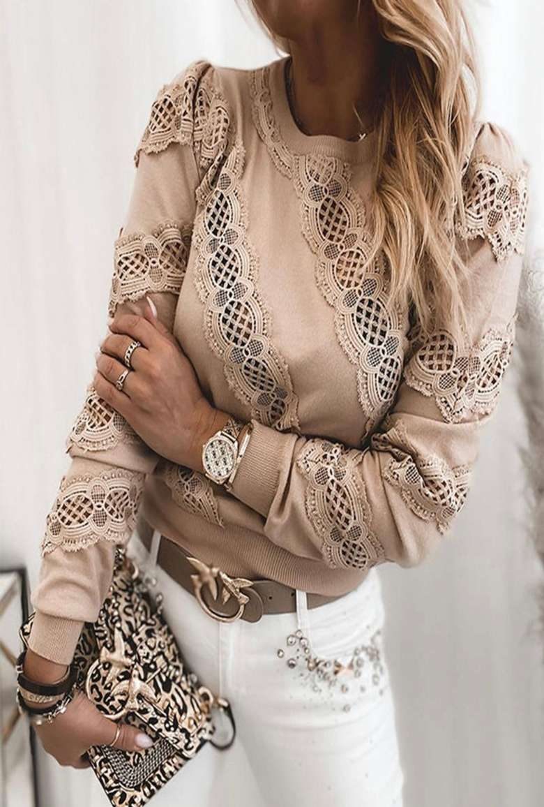 woman in a tan lace shirt holding a clutch and wearing white jeans