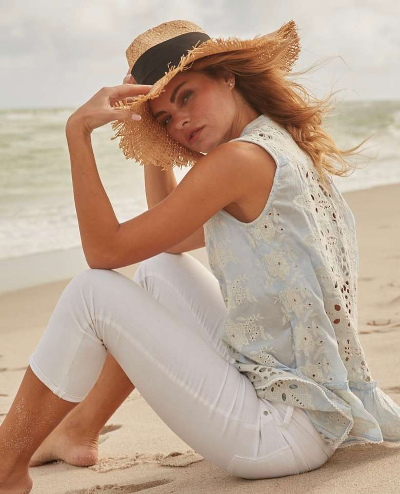 woman on a beach with eyelet top