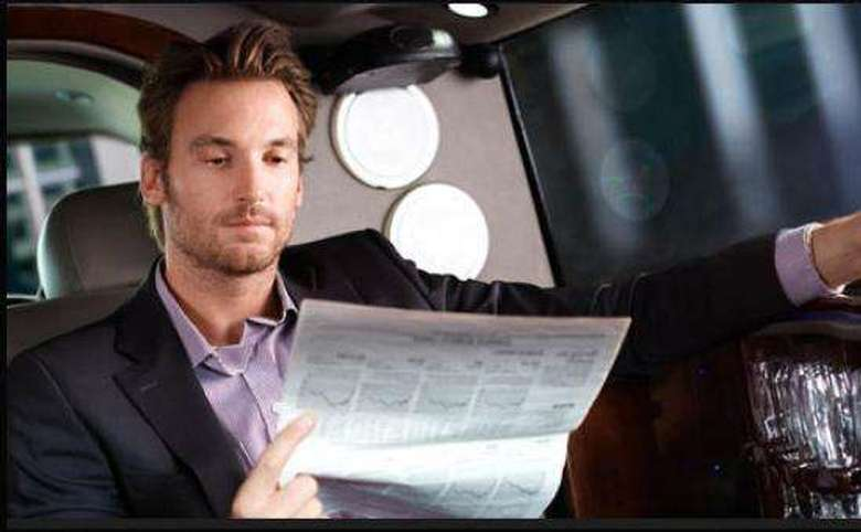 man reading the newspaper in the backseat of a car