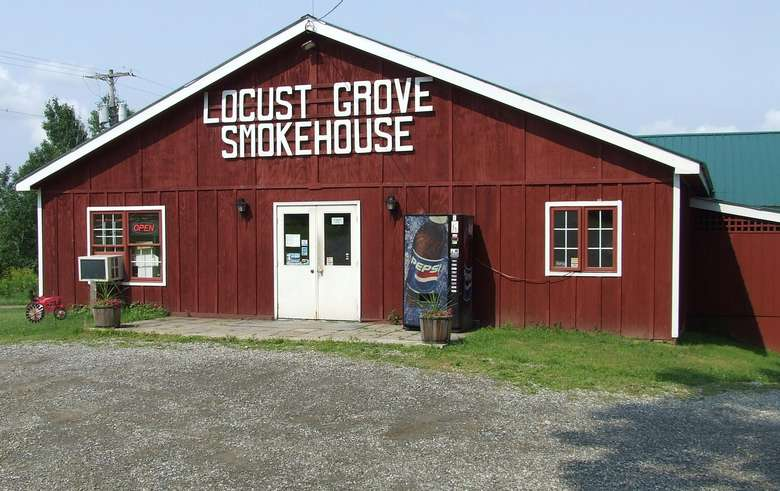 exterior of red barn with locust grove smokehouse in white letters