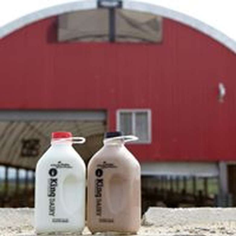 jug of regular and chocolate milk in front of a red barn