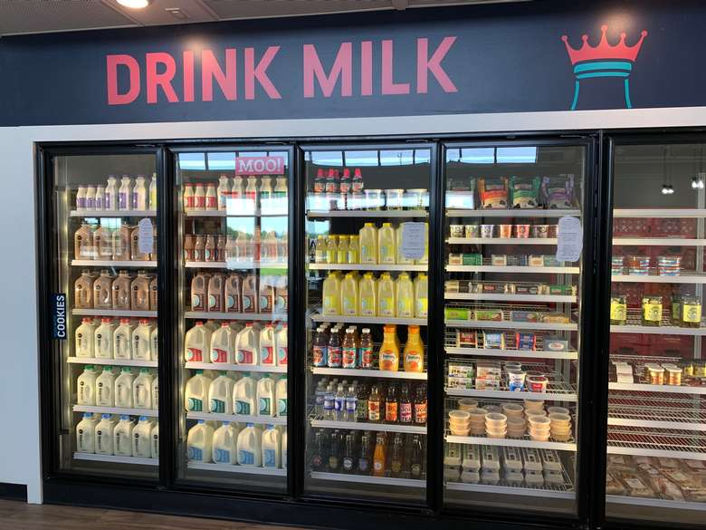 refrigerators full of milk and milk products with a sign that says drink milk