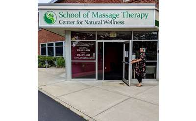 woman holding open door to building with sign for center for natural wellness