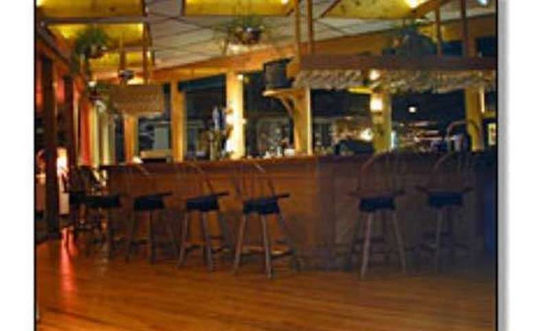an interior wooden wrap-around bar at the Shoreline Restaurant. There are wood floors and wooden stools.