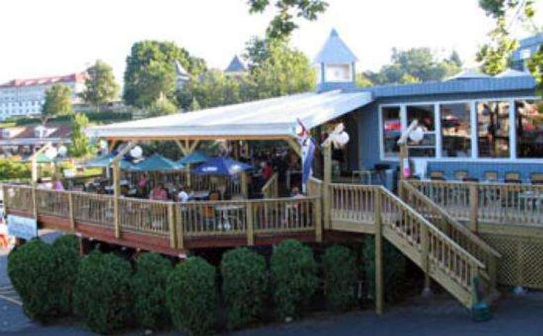 A staircase, and partially-covered outside deck at the Shoreline Restaurant. There are several outdoor dining tables and chairs, some with umbrellas.
