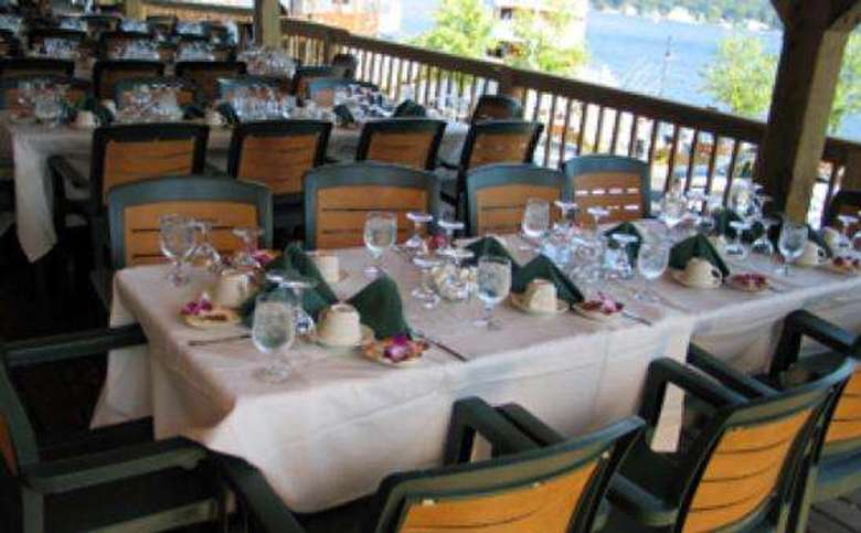 tables set for ten along a porch railing, overlooking the lake, which can be seen in the distance