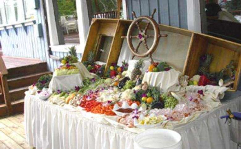 a buffet table decorated with a wooden boat and ship's steering wheel. There are several types of meats, vegetables and fruits on the table.