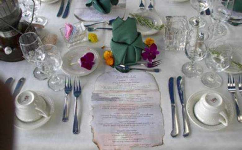 a place setting on a table with menu, decorative flowers, cups, glasses and cutlery