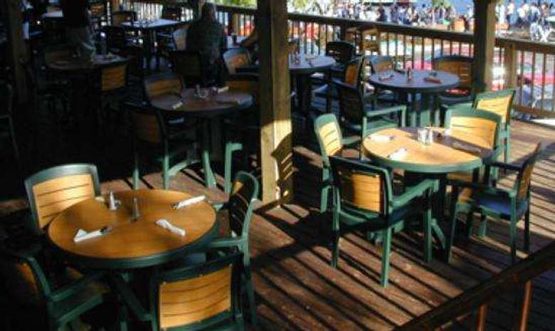 round wood and green tables for four, on a deck at the Shoreline Restaurant