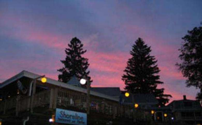 an exterior short of the Shoreline Restaurant with a beautiful red and pink sunset above it