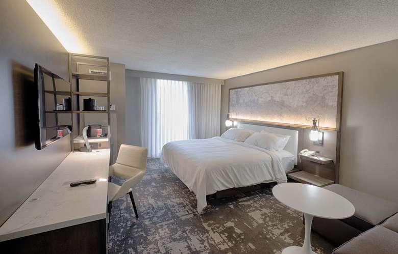 hotel room with one bed and a desk and table