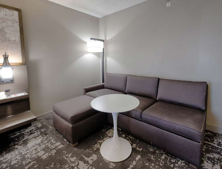 a small lounge area with a sofa and table in a hotel room
