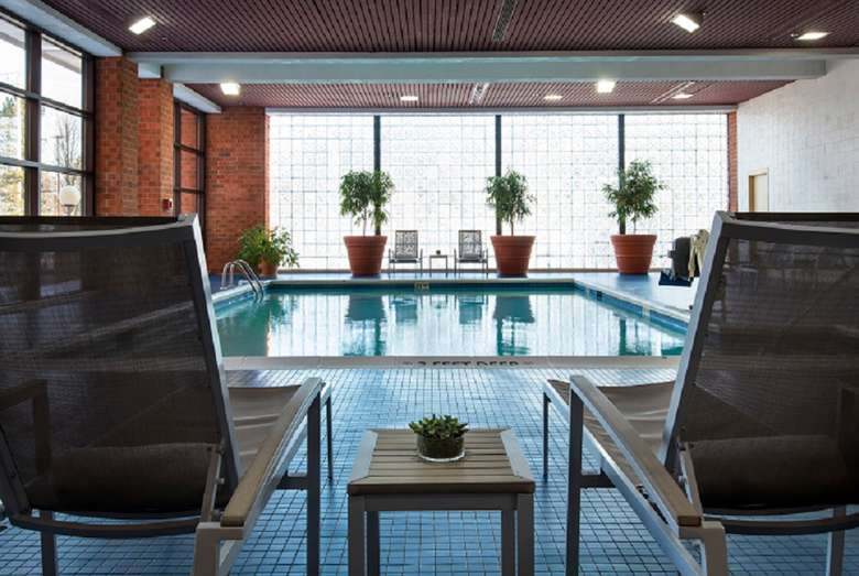 an outdoor pool in a hotel with some chairs around the edge