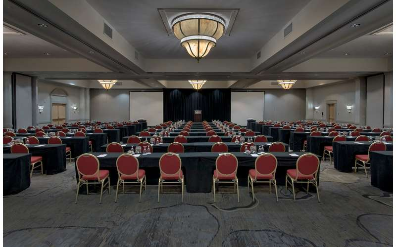 a large hotel event space with rows of chairs set up