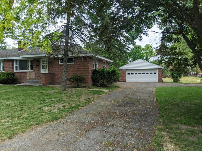a brick house with a paved driveway and a garage