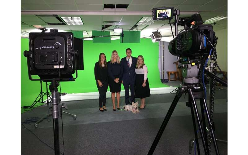 four people in front of green screen and cameras