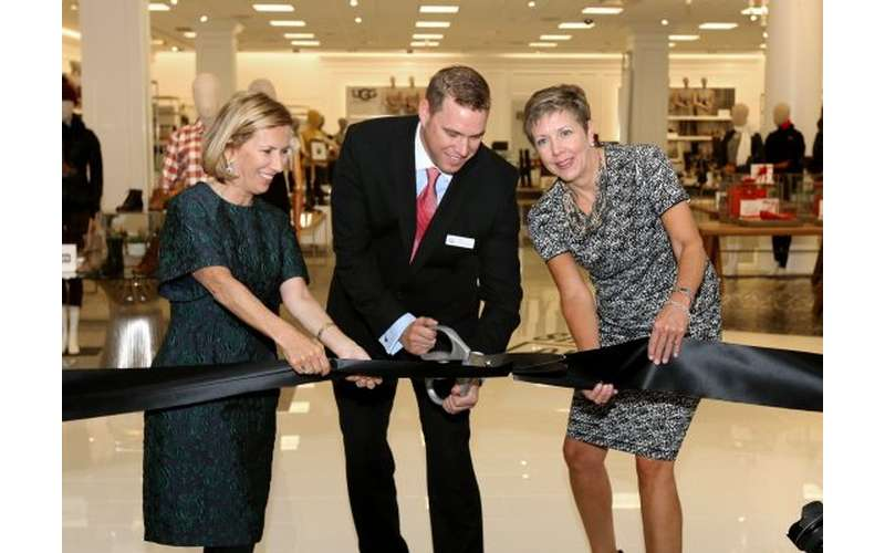 three people performing a ribbon cutting in front of a store