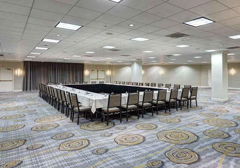 large banquet room in a hotel with tables and chairs set up in a square for a meeting