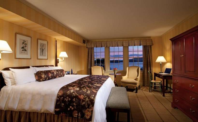 a hotel bedroom with waterfront views and a large bed