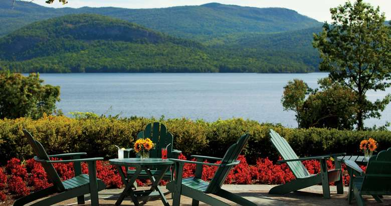 view of the lake from a patio area filled with green adirondack chairs