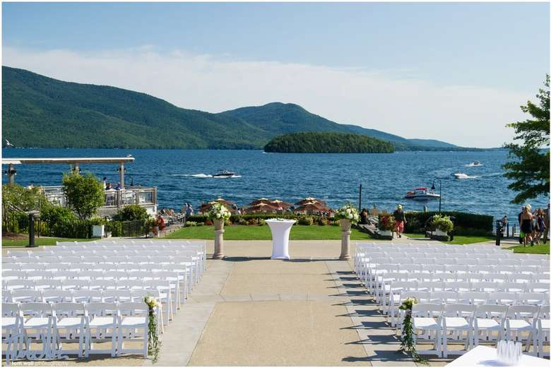 rows of white chairs set up from a waterfront wedding ceremony