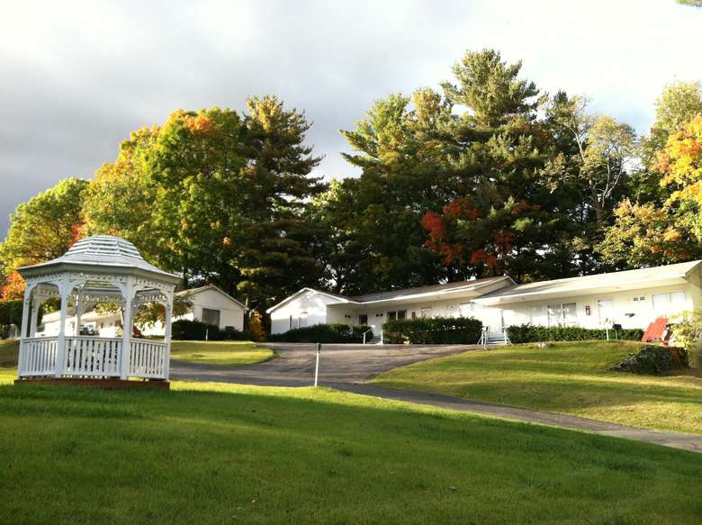 gazebo in a yard with white buildings in the background