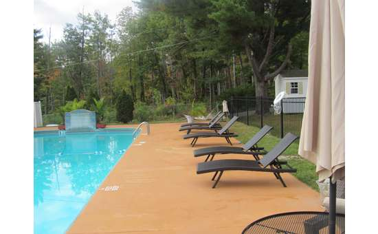 lounge chairs next to an outdoor pool