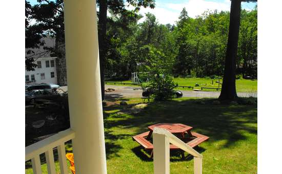 view from a porch of a picnic table and green grass surrounded by trees