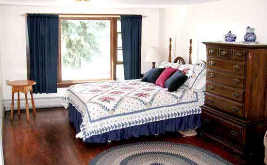 a bedroom with hardwood floors, bed with decorative quilt, large wooden chest of drawers and large window with blue drapes