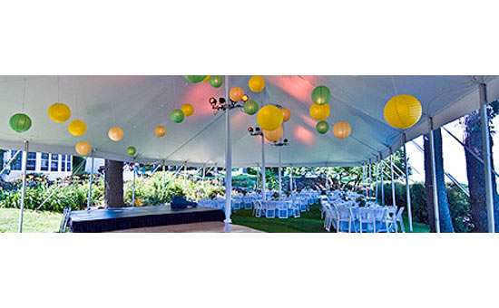 the inside of a white outdoor wedding reception tent with white tables and chairs and colorful, round light fixtures hanging from the ceiling of the tent