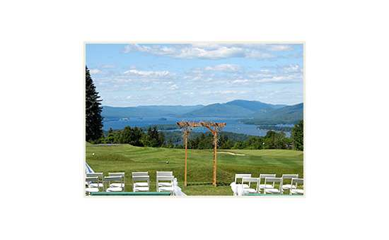 a green lawn set with white chairs and a wooden trellis for an outdoor wedding ceremony with the forest, lake and mountains in the background