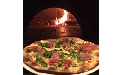 a wood fired pizza near the open oven