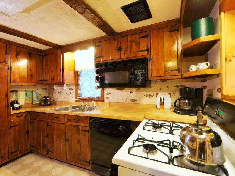 kitchen with stove, cabinets, tea kettle
