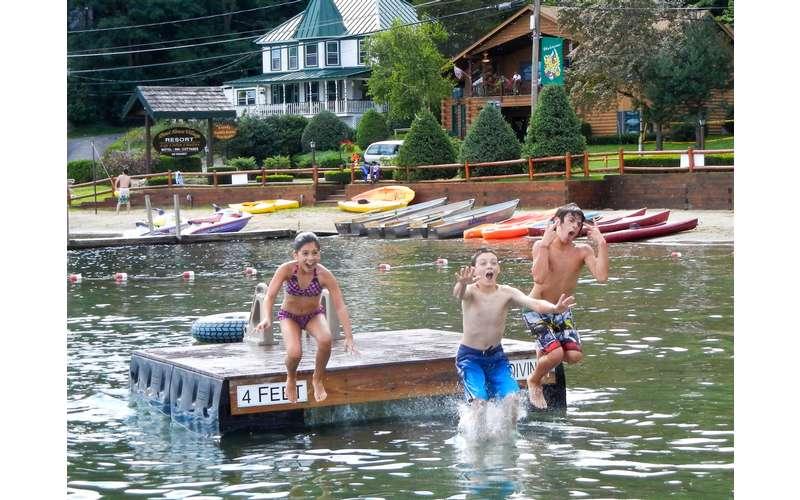 three kids jumping off floating dock