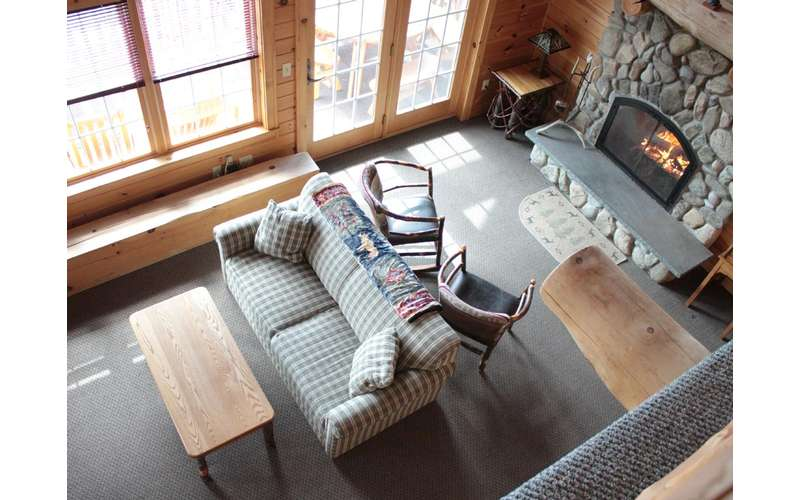 looking down from upstairs into a quaint living room with stone fireplace