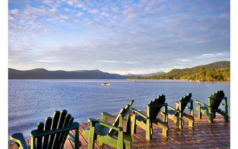 green Adirondack chairs lined up facing the lake