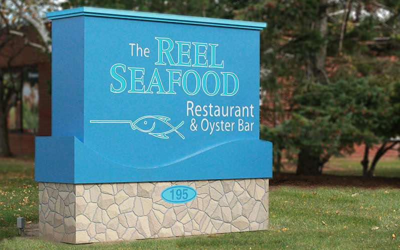sign outside reel seafood co.