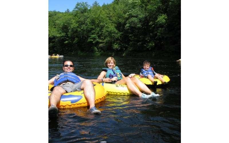 three people on river tubes