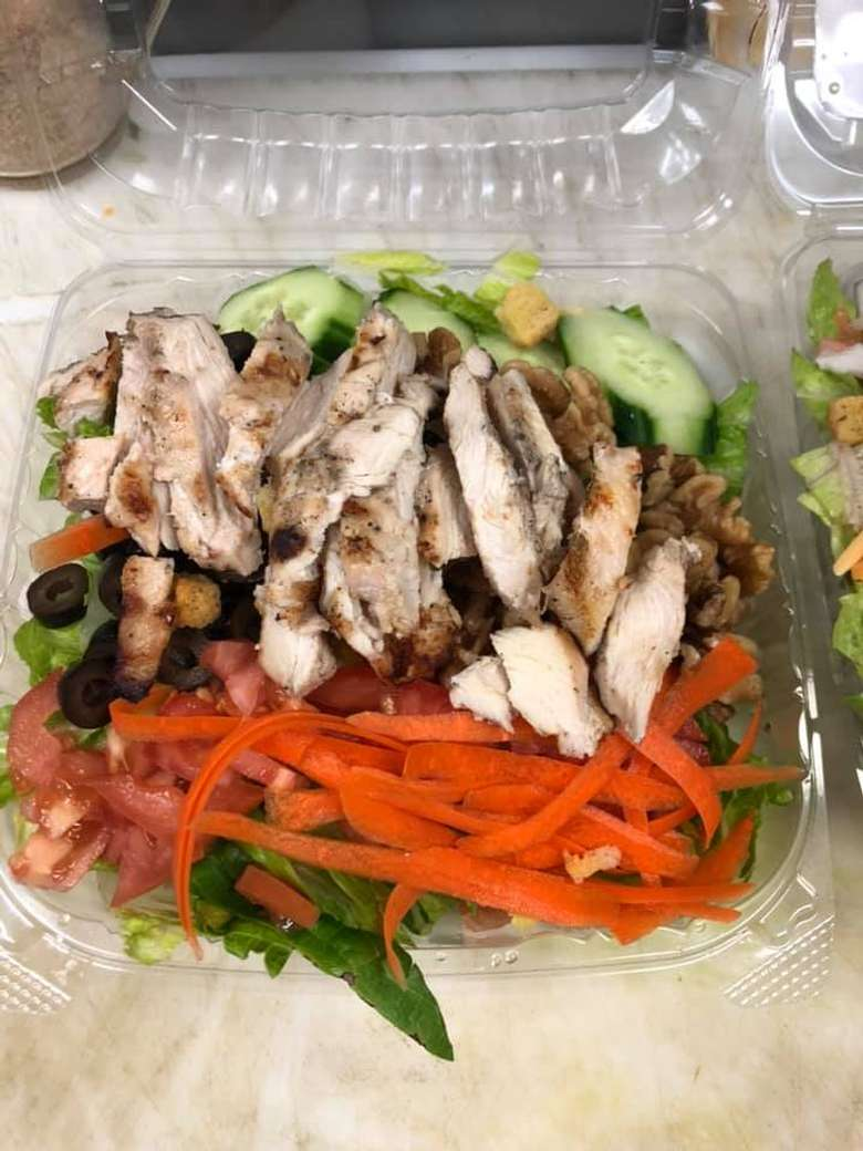 salad with chicken in a plastic takeout container
