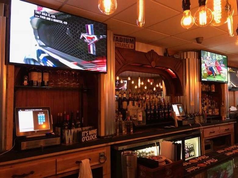 two tvs above a bar